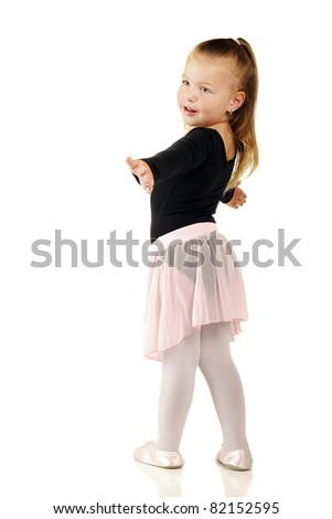 A pretty little girl preparing to spin in her ballerina outfit.  Isolated on white. - stock photo