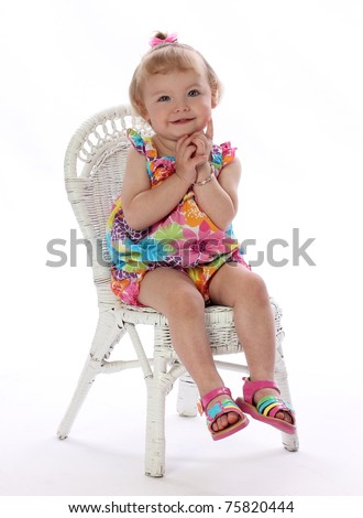A Pretty Little Girl Sits Calmly in a Chair - stock photo