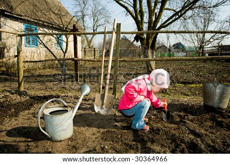 A pretty little girl squatting down on the ground in  her grandfather's  kitchen garden  cultivating soil with  a toy  spade