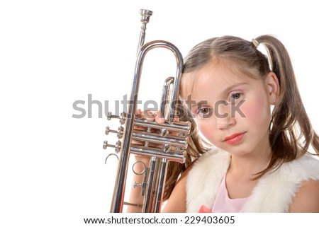 a pretty little girl with a trumpet look at the camera on the white background - stock photo