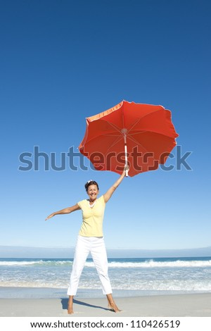 A pretty looking mature woman dancing happy and cheerful with big orange umbrella at beach, isolated with ocean and blue sky as background and copy space.