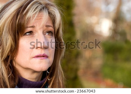 A pretty middle aged woman looking upwards. - stock photo
