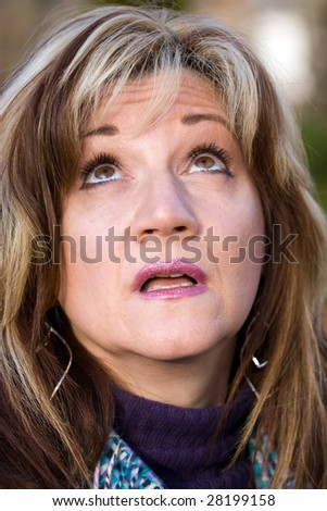 A pretty middle aged woman looking upwards in confusion. - stock photo