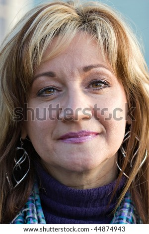 A pretty middle aged woman with a very sincere smile. Shallow depth of field. - stock photo