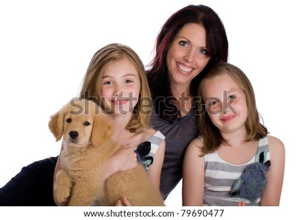 a pretty Mother and her two daughters with a Golden Retriever Puppy.