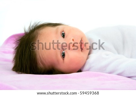 A pretty newborn baby girl on pink blanket against a white background