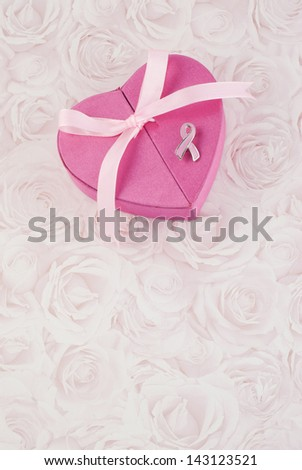 A pretty pink gift box decorated with a pink bow and pink pin to represent  Breast Cancer Awareness - stock photo