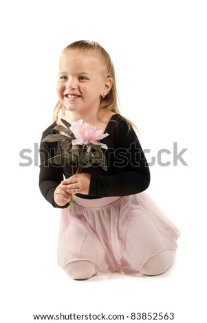 A pretty preschool ballerina holding a large, pink flower.  Isolated on white. - stock photo