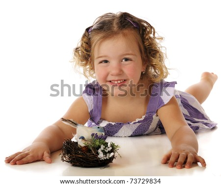 A pretty preschooler happy with a little bird's nest.  Isolated on white. - stock photo