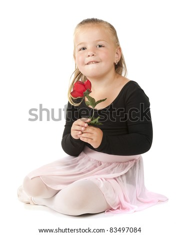 A pretty preschooler holding a single red rose while in her ballet outfit.  Isolated on white. - stock photo