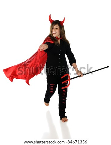 A pretty preteen girl running and pointing forward in a devil costume.  Isolated on white. - stock photo