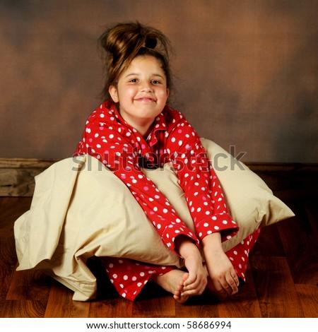 pretty preteen girl sitting on a wood floor in polka-dot pajamas ...