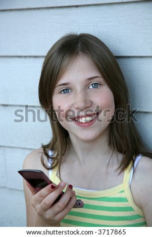 a pretty preteen girl with her cell phone in hand - stock photo