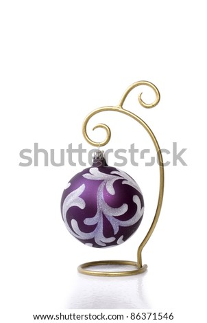 A pretty purple Christmas ball ornament hanging on a gold ornament hanger against a bright white background with a mild reflection/shadow beneath with plenty of copy space.