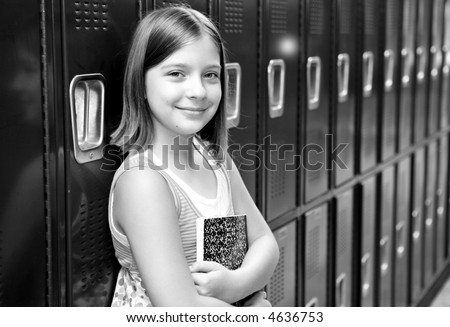 A pretty school girl leaning against her locker. Black and white. - stock photo