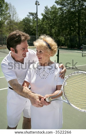 A pretty senior woman getting a tennis lesson from a handsome young pro.