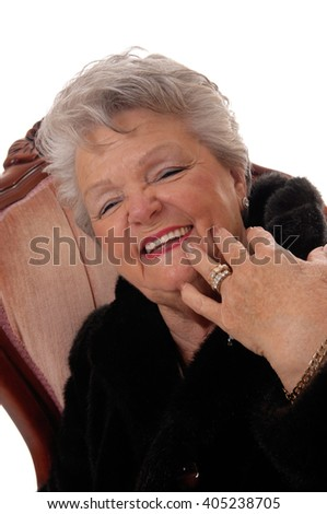 A pretty senior woman in a black fur coat laughing with her mouth open,