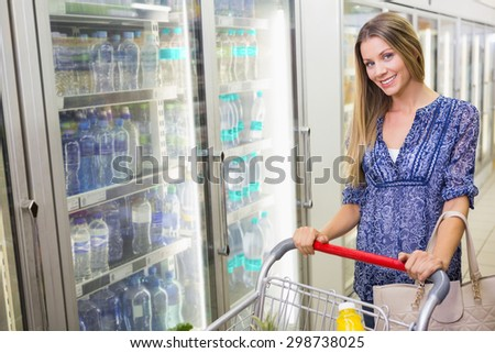 A pretty smiling blonde woman buying frozen products at supermarket