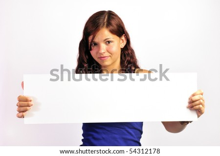 A pretty, smiling girl holding up a long blank white board, focus is on the board so its easy to add your own text.