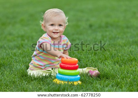 A pretty smiling little girl sitting on the green grass is playing with a toy pyramid - stock photo