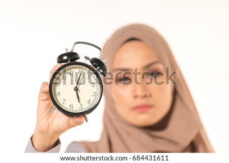 A pretty student holding clock. Time management concept.