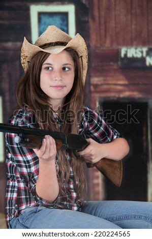 A pretty teen cowgirl holding her rifle in front of a rustic western building.   - stock photo