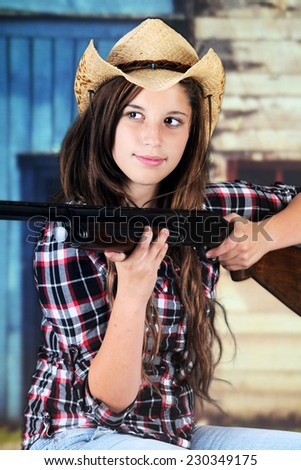 A pretty teen cowgirl taking aim with her rifle. - stock photo