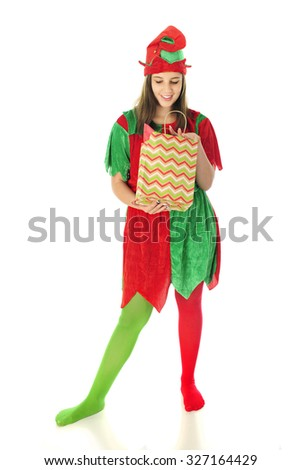 A pretty teen elf happily looking inside a chevron-patterned Christmas gift bag.  On a white background. - stock photo