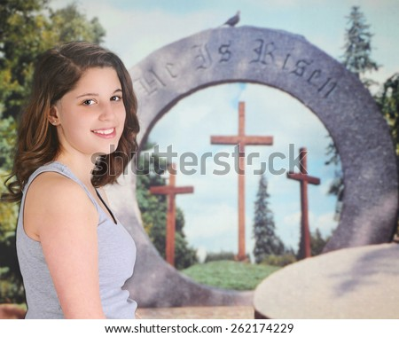 A pretty teen girl delighted before an Easter resurrection display.   - stock photo