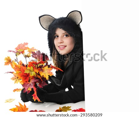A pretty teen girl dressed as a back cat.  She's holding a bouquet of fall leaves and looking around a white sign left blank for your text.  On a white background.