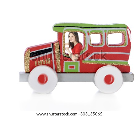"""A pretty teen girl """"driving"""" a  red, green and sparkly gold car cutout.  Radial blur on wheels.   On a white background. - stock photo"""