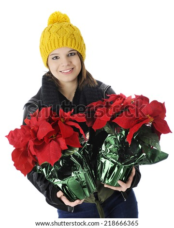 A pretty teen girl happily carrying two pots of poinsettias.  On a white background. - stock photo
