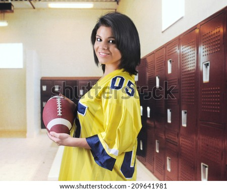 A pretty teen girl happily holding a football in an empty locker room.   - stock photo