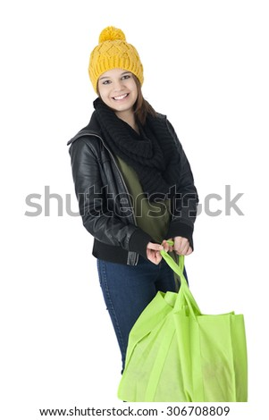 A pretty teen girl in yellow ski cap and black leather jacket happily carrying a cloth shopping bag.  On a white background. - stock photo