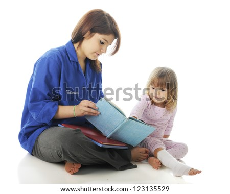 A pretty teen volunteer reading a story to an injured preschooler.  On a white background. - stock photo