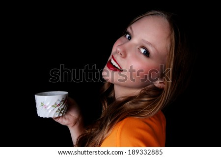 A pretty teenage girl holding a coffee cup and smiling, isolated for black background.  - stock photo