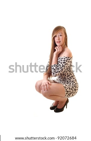 A pretty teenage girl in a short leopard print dress crouching on the floor with her long brunette hair and in high heels, for white background. - stock photo