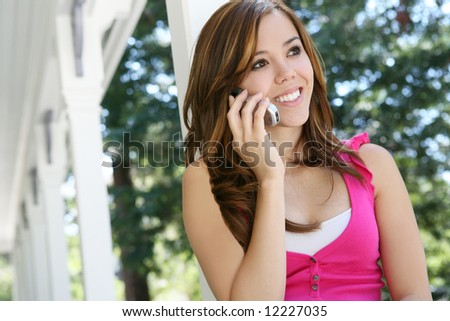 A pretty teenage girl on the cell phone at home - stock photo