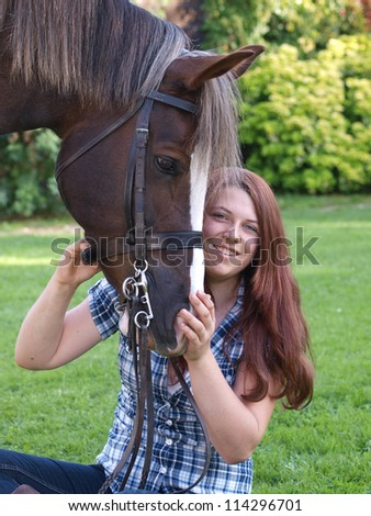 A pretty teenage girl sits with her horse - stock photo