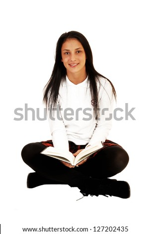 A pretty teenager girl in her school uniform and long black hair sitting on the floor with a book in her hands for white background. - stock photo