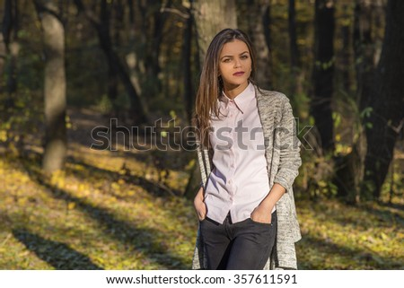 A pretty teenager girl is posing in an autumn oak forest at afternoon. She has a detached and thoughtful expression on her face. She is holding her hands in her jeans pockets.