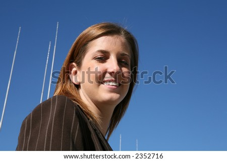 A pretty television reporter with antenna in the background - stock photo