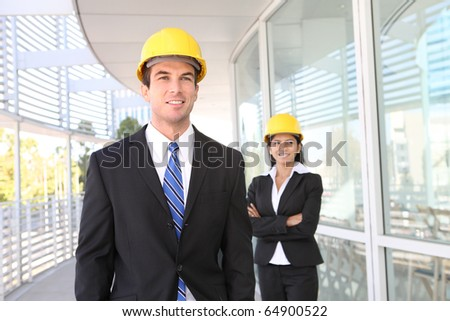 A pretty woman and handsome man architects on building construction site - stock photo