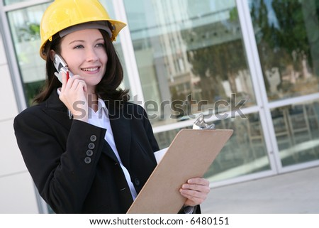 A pretty woman architect holding blueprints and talking on the phone