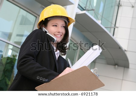 A pretty woman architect holding blueprints and talking on the phone - stock photo