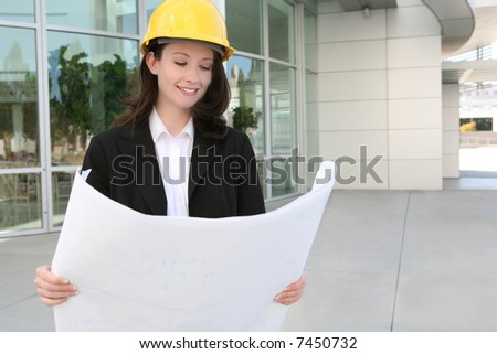 A pretty woman architect inspecting the blueprints - stock photo