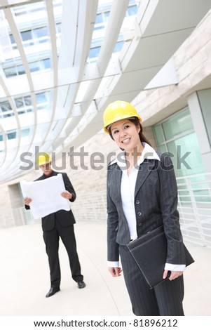 A pretty woman asian architect on work site with male co-worker in background