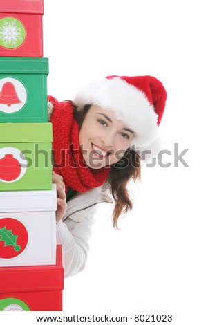 A pretty woman at Christmas hiding behind presents - stock photo