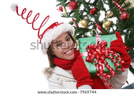 A pretty woman at Christmas holding a present by the tree