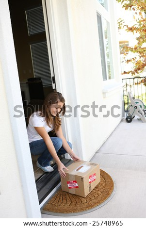A pretty woman at home picking up delivery box package